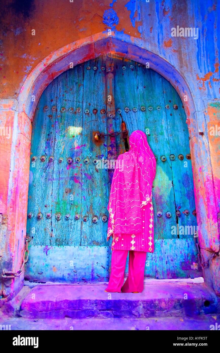Mujer en vieja Delhi por un colorido puerta, India Foto de stock