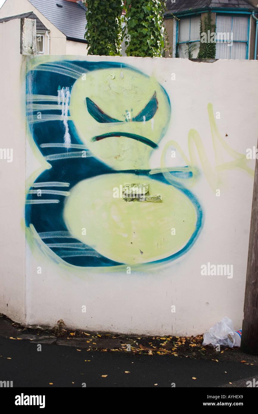 Graffiti de un gruñón enojado cara sobre el muro de un jardín Cardiff UK Foto de stock