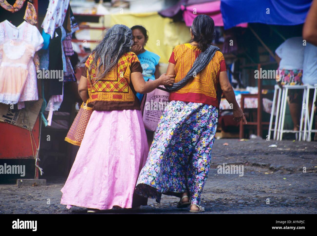 bc6b377cd Una pareja de mujeres caminando por el mercado vestidos con tradicionales  elaboradamente bordado rojo y oro