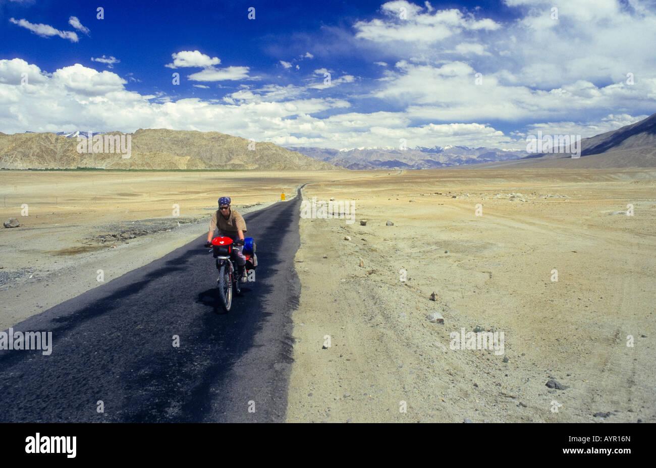 Ciclista vistiendo mantilla montando bicicleta completamente cargado abajo de un solo tramo de autopista del desierto, Imagen De Stock