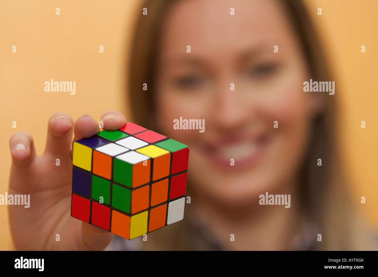 Una mujer con un cubo de colores en la mano Foto de stock