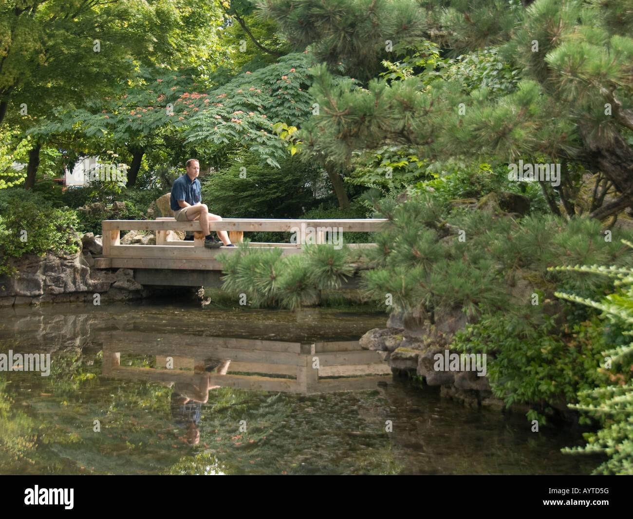 Un hombre solitario se sienta y contempla en un jardín chino. Imagen De Stock