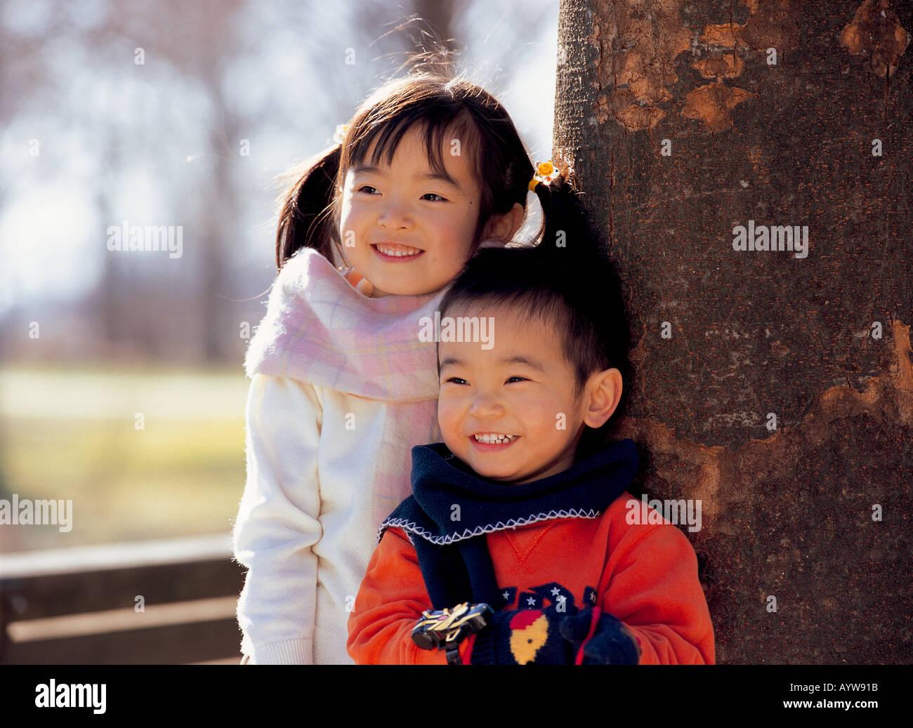 Niña con su hermano de pie junto a un árbol Foto de stock