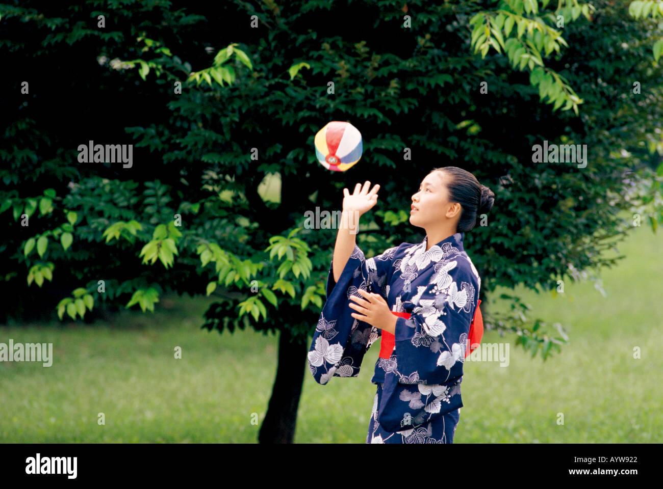 Chica en kimono jugando con globos de papel Foto de stock