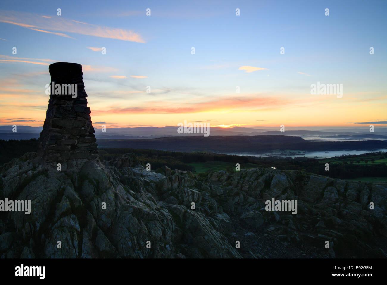 Cairn trig punto en la parte superior de 'cómo' Gummers al amanecer, Lake District, Cumbria, Inglaterra. Foto de stock