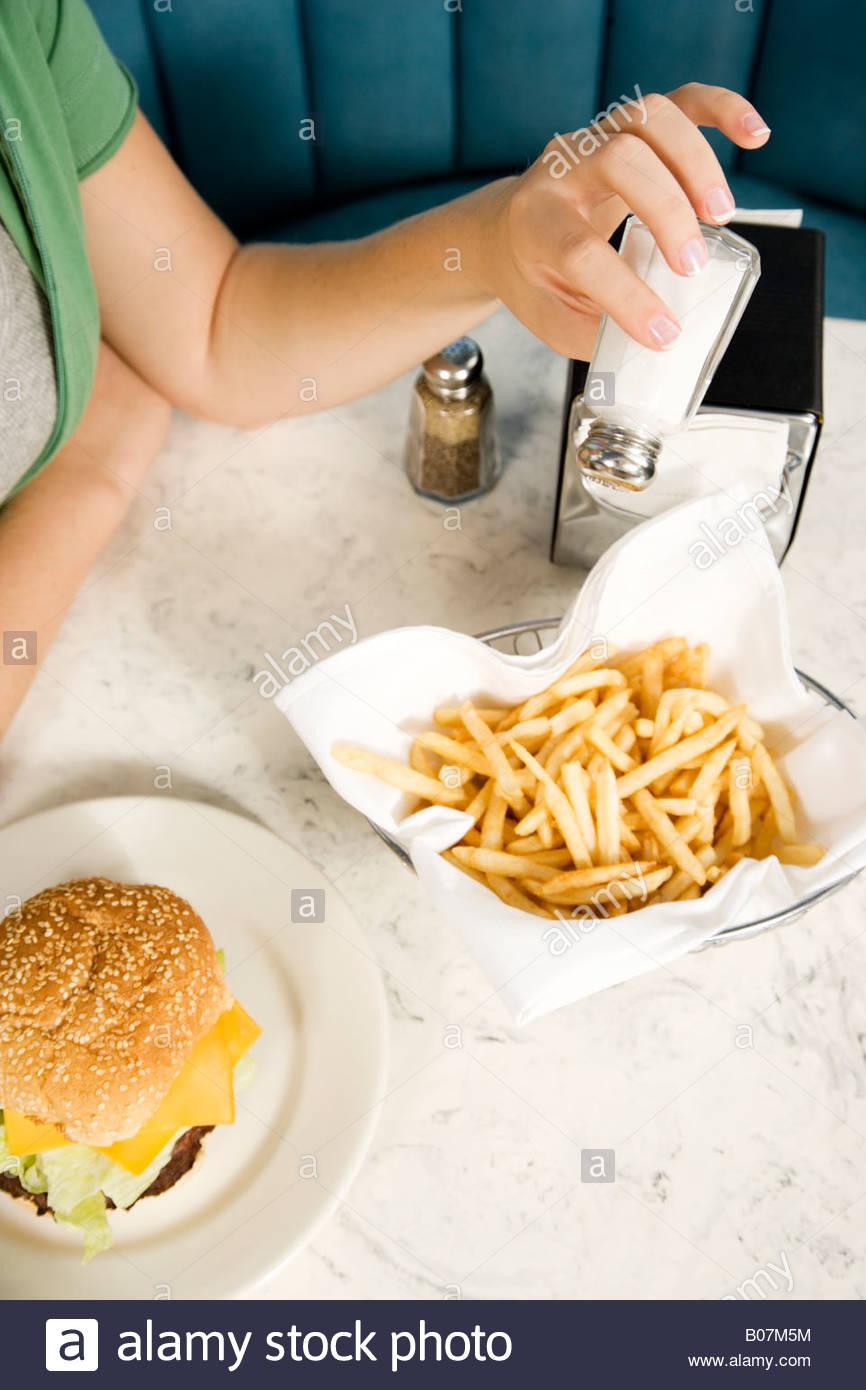 Cerca de una chica poniendo sal en sus patatas fritas Imagen De Stock