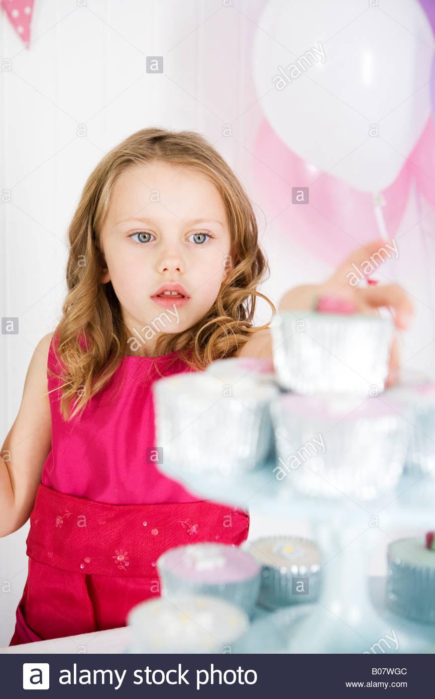 Chica en teniendo torta cake stand en la fiesta de cumpleaños Imagen De Stock
