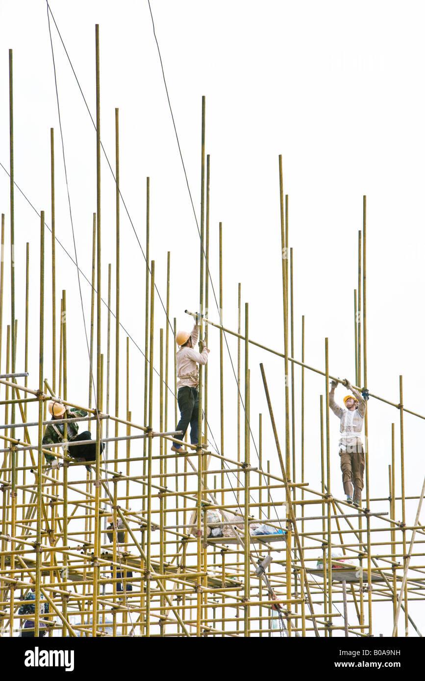 Los trabajadores de la construcción en los andamios, bajo ángulo de visión Imagen De Stock