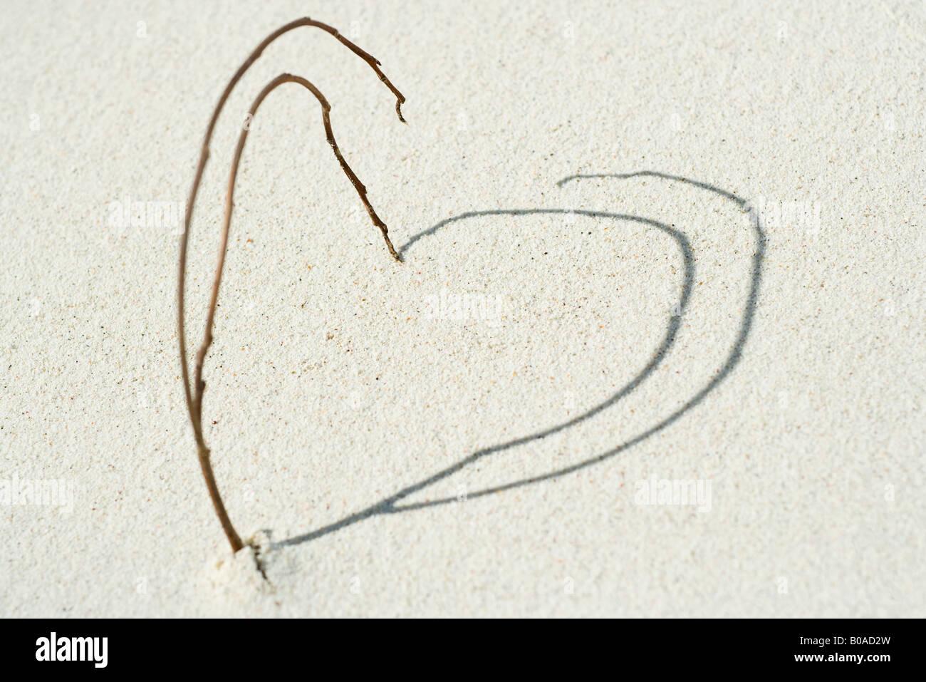 Las ramitas y las sombras dispuestas en forma de corazón en la playa, cerca de la Foto de stock