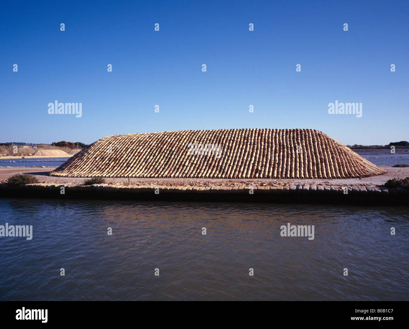 Los montones de sal de mar protegida por baldosas de terracota cerca de Trapani o Masala Sicilia Italia UE Abril Imagen De Stock