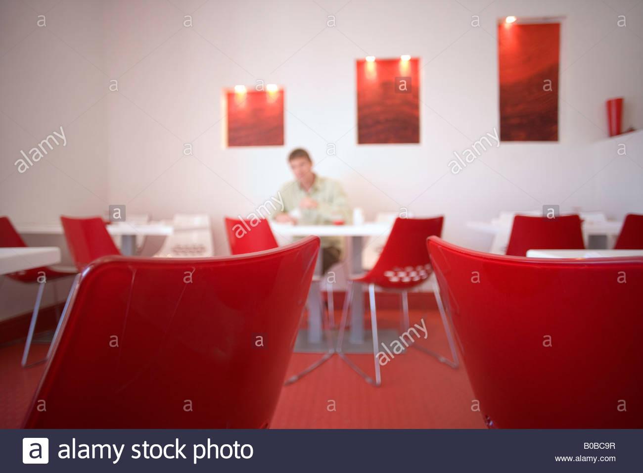 Hombre sentado a la mesa en la moderna cafetería con decoración en blanco y rojo, se centran en la mesa Imagen De Stock