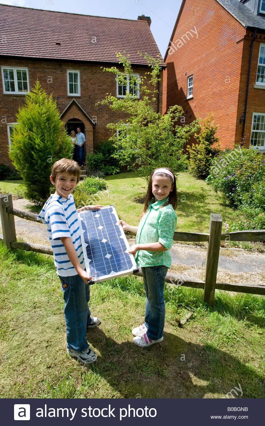 Hermano y hermana con panel solar por casa, Retrato Imagen De Stock