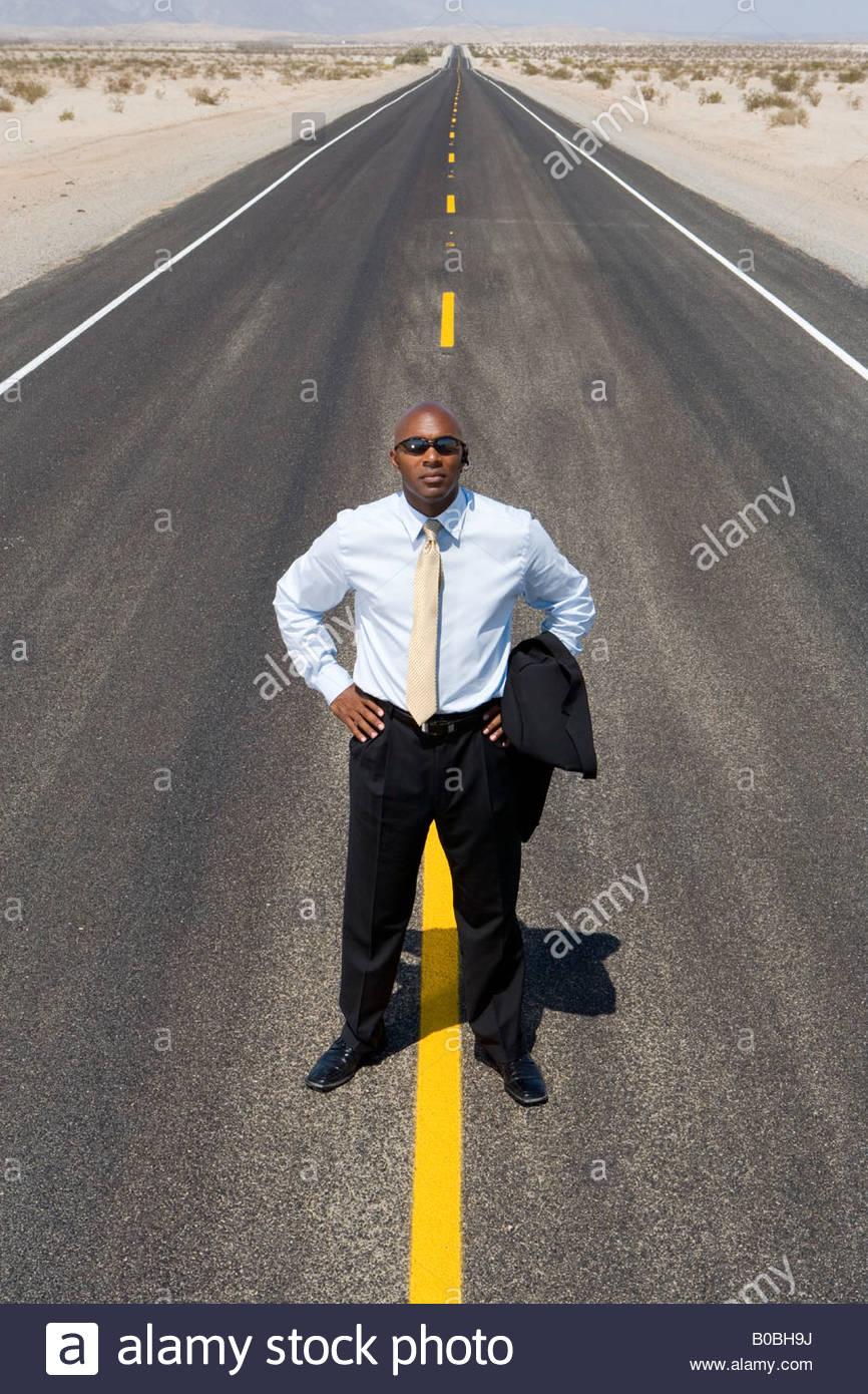 Hombre de negocios en línea en medio del camino en el desierto, las manos en las caderas, niveles elevados Imagen De Stock