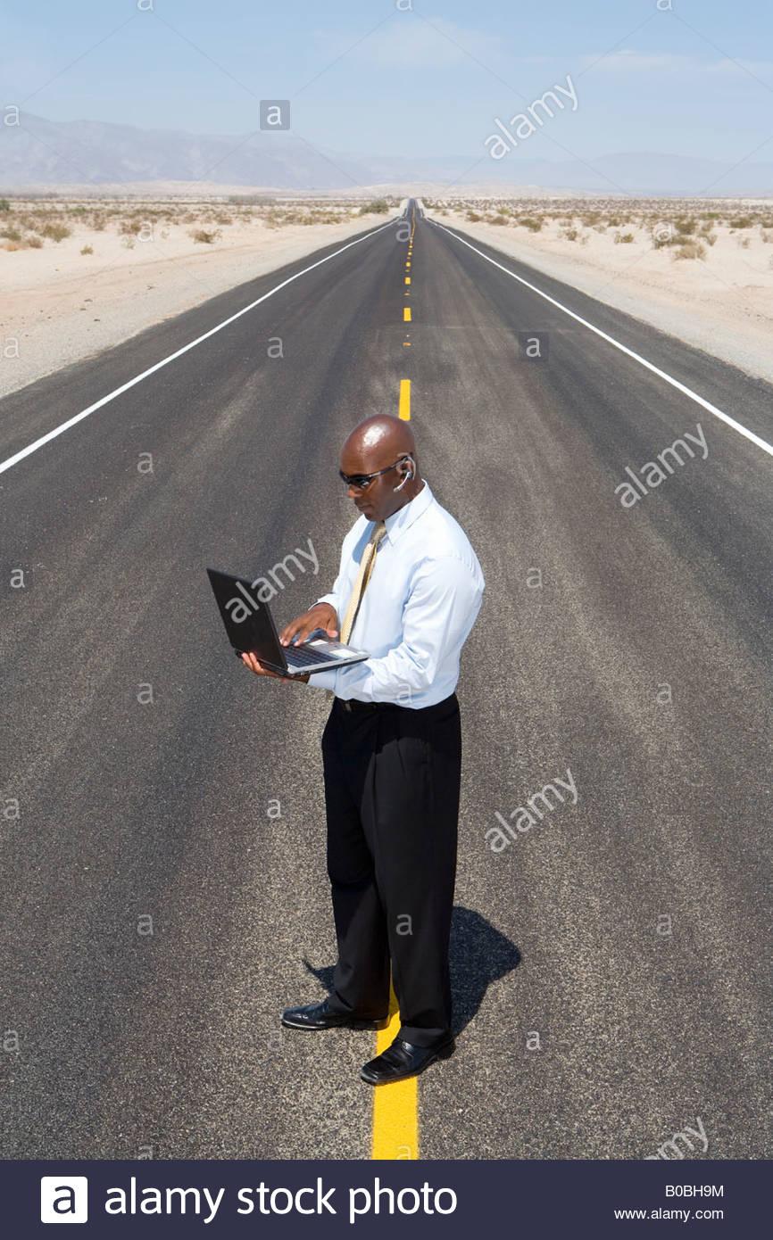 Hombre de negocios en línea en medio del camino en el desierto, utilizando equipo portátil, vista elevada Imagen De Stock