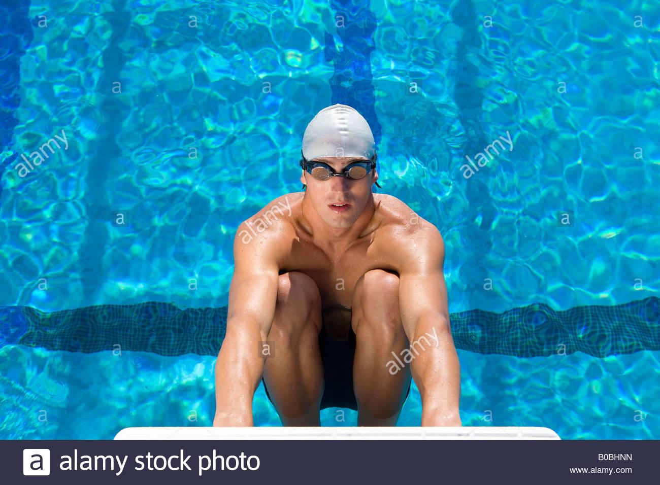 Nadador masculino en bloque inicial, vista elevada Imagen De Stock