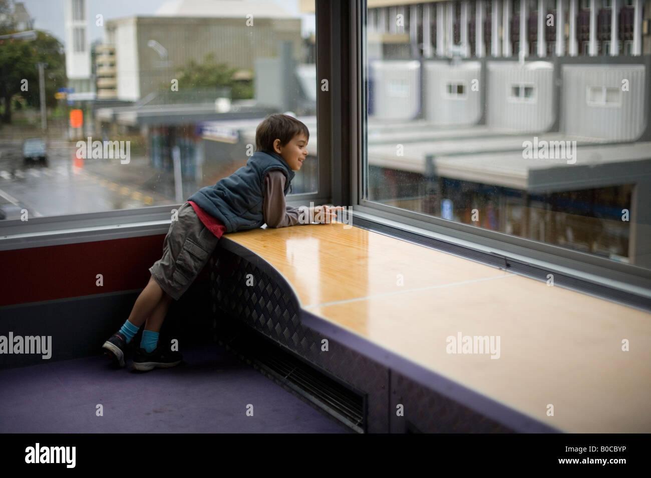 A partir de seis años chico mira por la ventana Biblioteca, Palmerston North, Nueva Zelanda Imagen De Stock