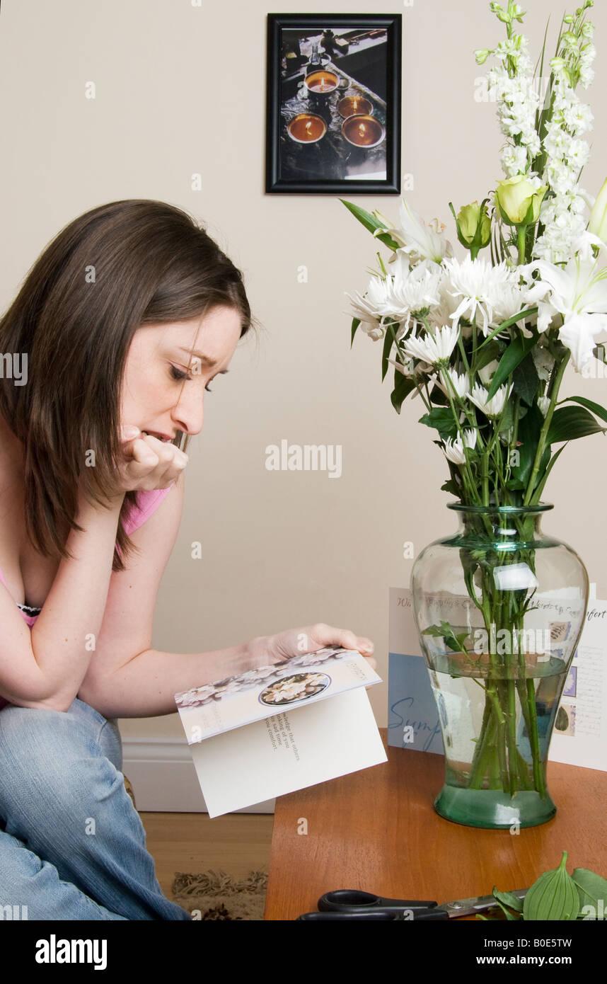 Recientemente afligida joven viendo una tarjeta de pésame con floweres Imagen De Stock