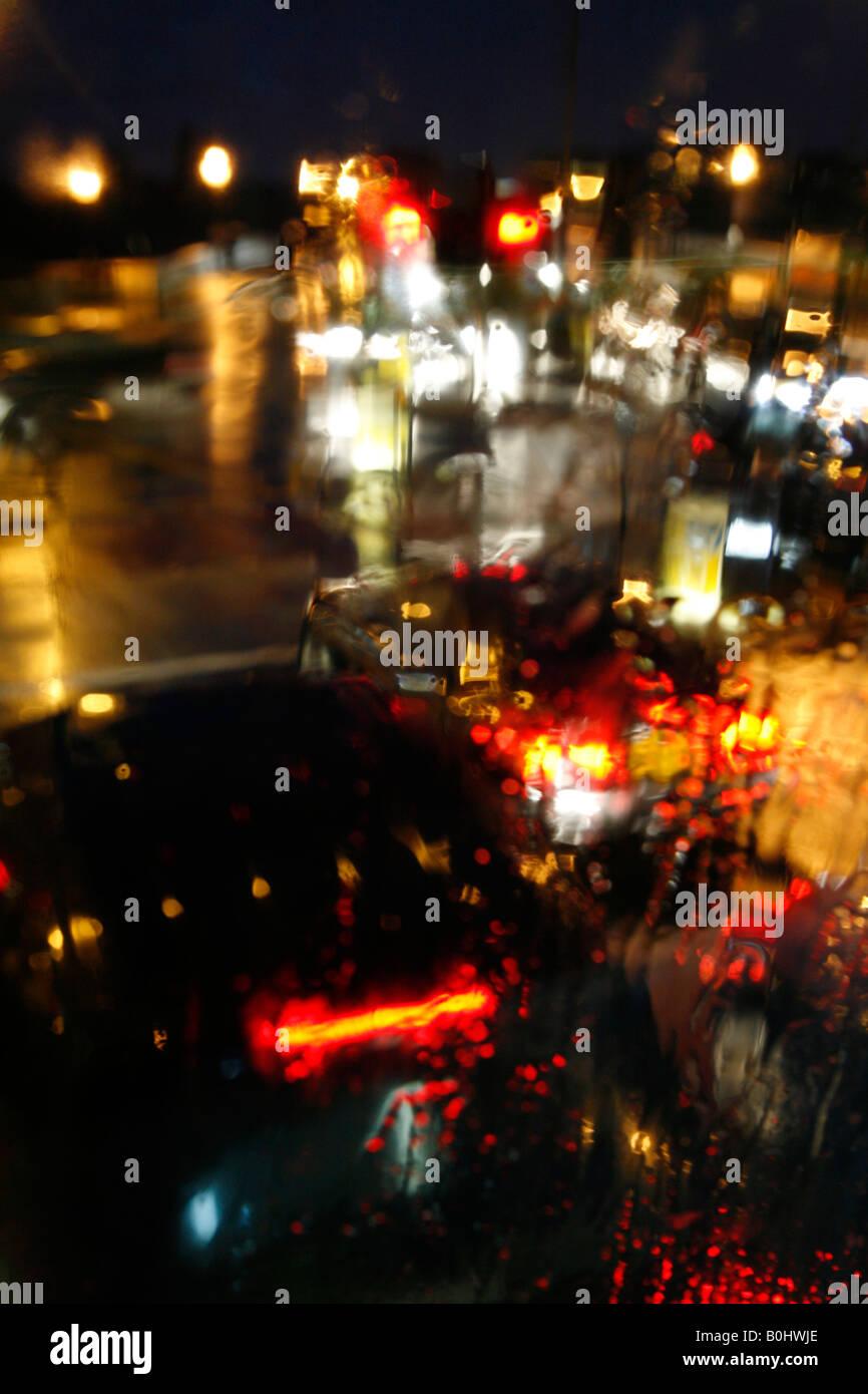 Cola de tráfico esperando en el semáforo en un lluvioso Putney High Street, Putney, Londres Imagen De Stock