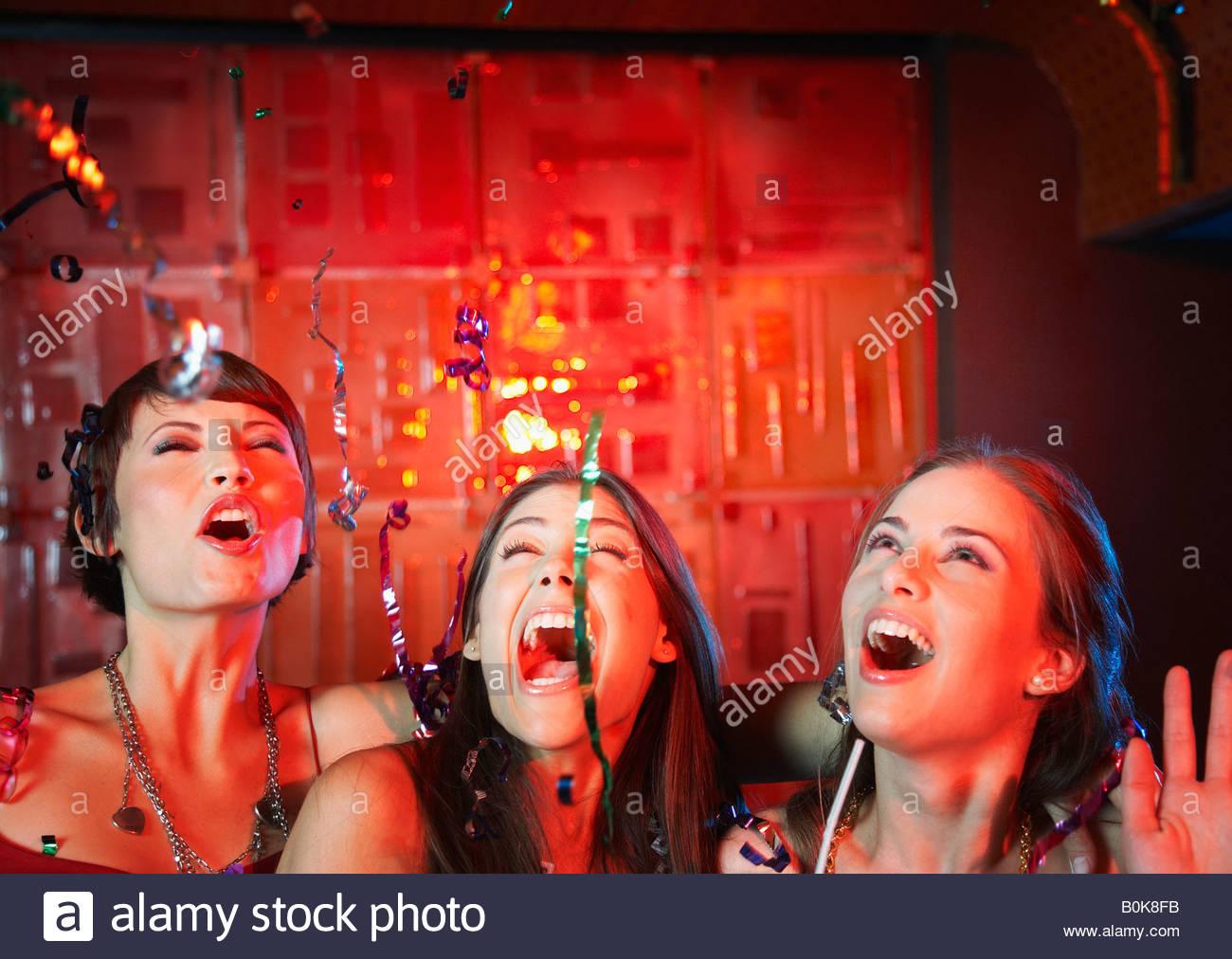 Tres mujeres en una discoteca bebiendo y riendo Foto de stock
