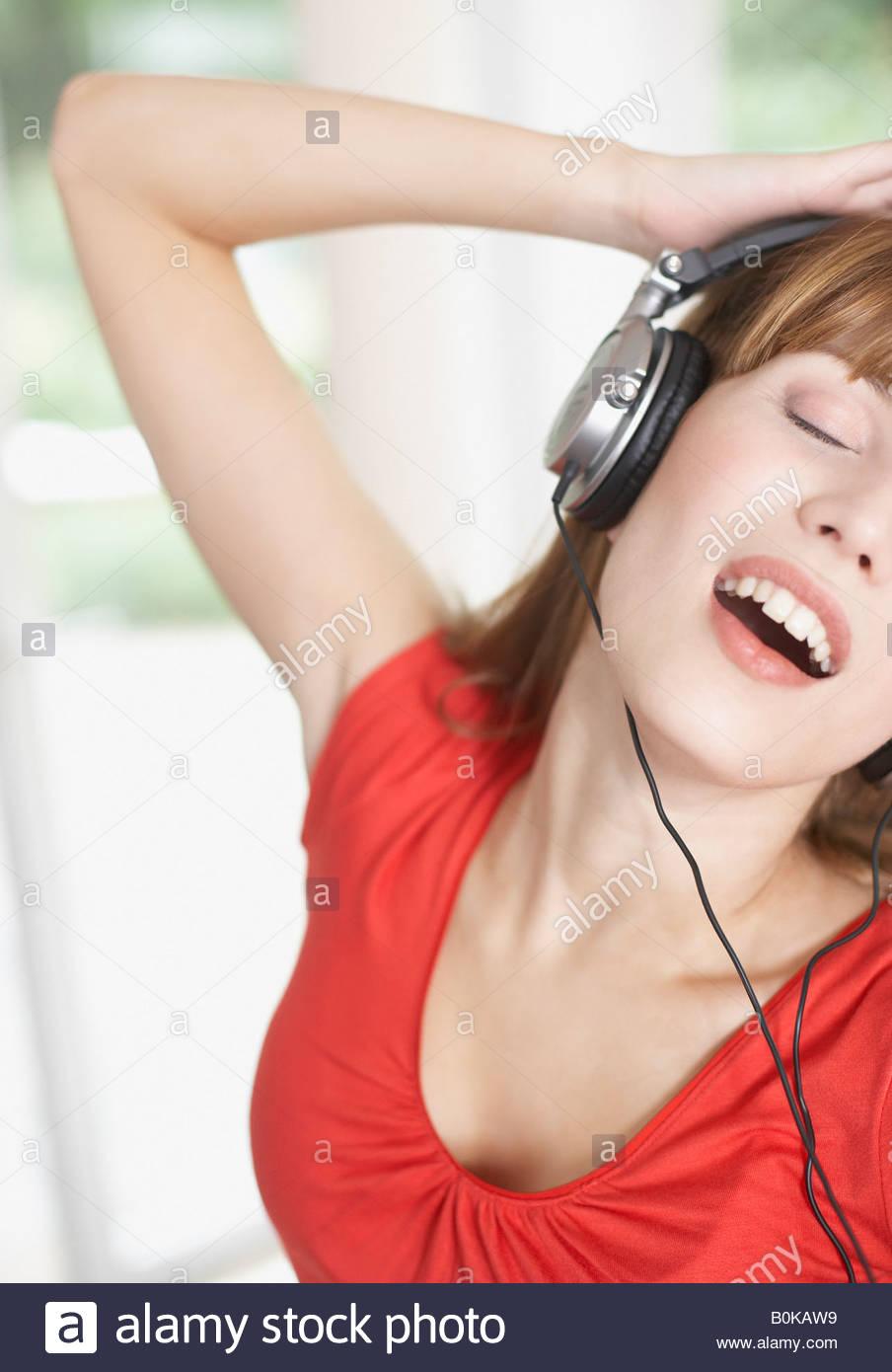 Mujer usando audífonos y baile Imagen De Stock