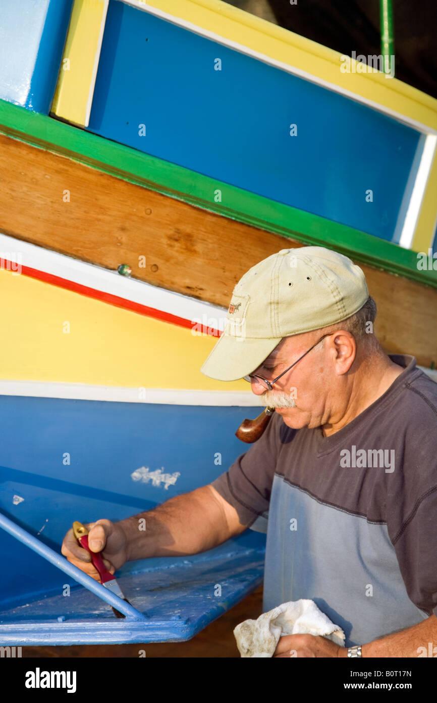 El hombre pintando un luzzu, ojos pintados en la parte delantera para proteger a los pescadores cuando están Imagen De Stock