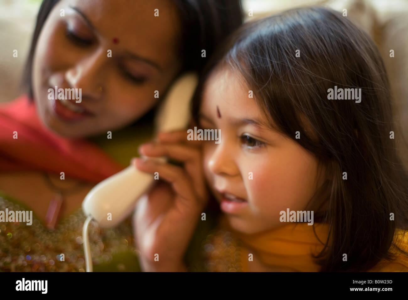 Madre pakistaní y la hija de raza mixta en la vestimenta tradicional teléfono home Imagen De Stock