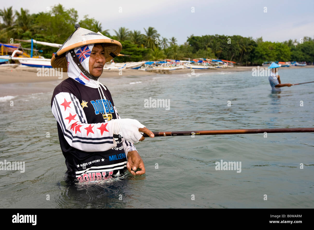 Viejo pescador de pie en el mar cerca de Senggigi pesca de peces pequeños utilizando los métodos tradicionales, Imagen De Stock