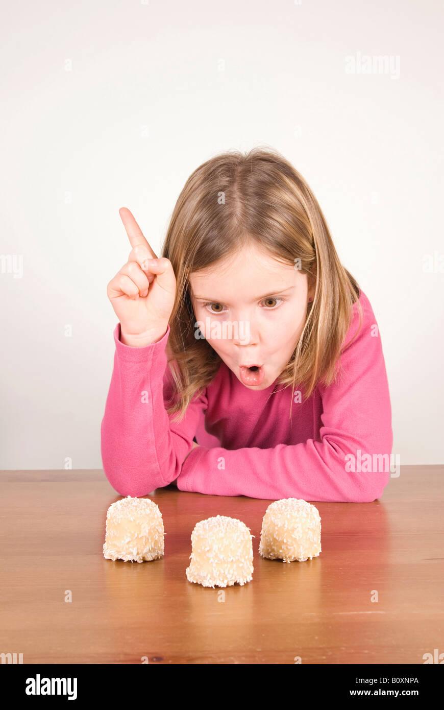 Chica (6-7) mirando el chocolate malvaviscos, engañando a unos Imagen De Stock