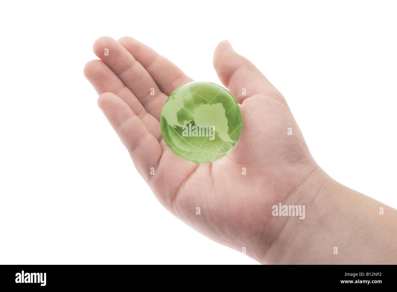 Globo de Cristal verde en la palma de la mano del niño sobre fondo blanco. Imagen De Stock