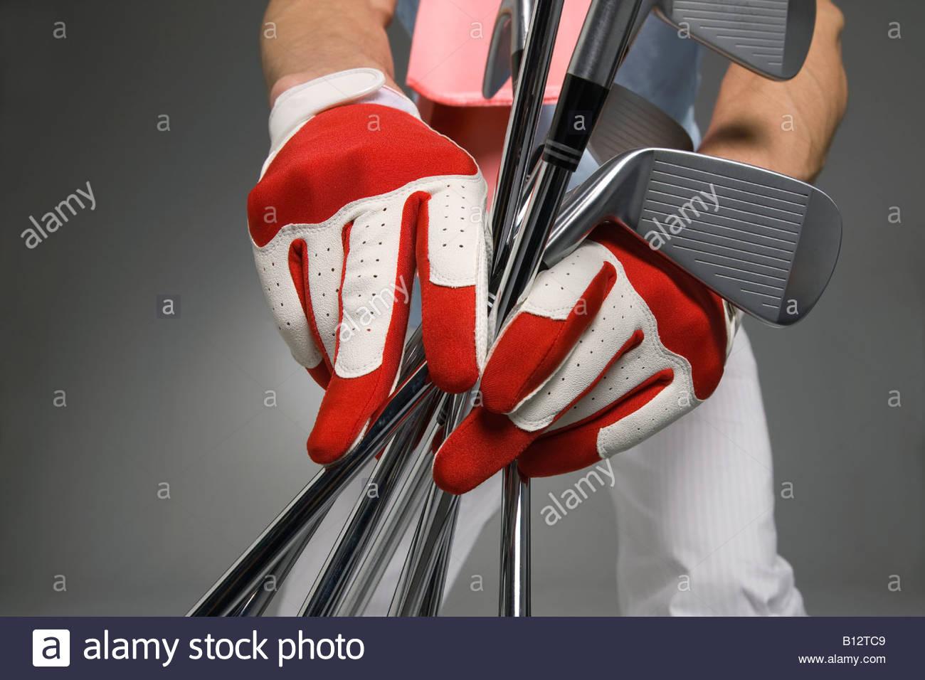 Central vista de joven sosteniendo los palos de golf, Foto de estudio Imagen De Stock
