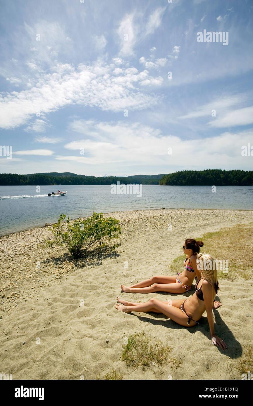Las mujeres jóvenes en la playa en el lago McIvor. Campbell River, la isla de Vancouver, British Columbia, Imagen De Stock