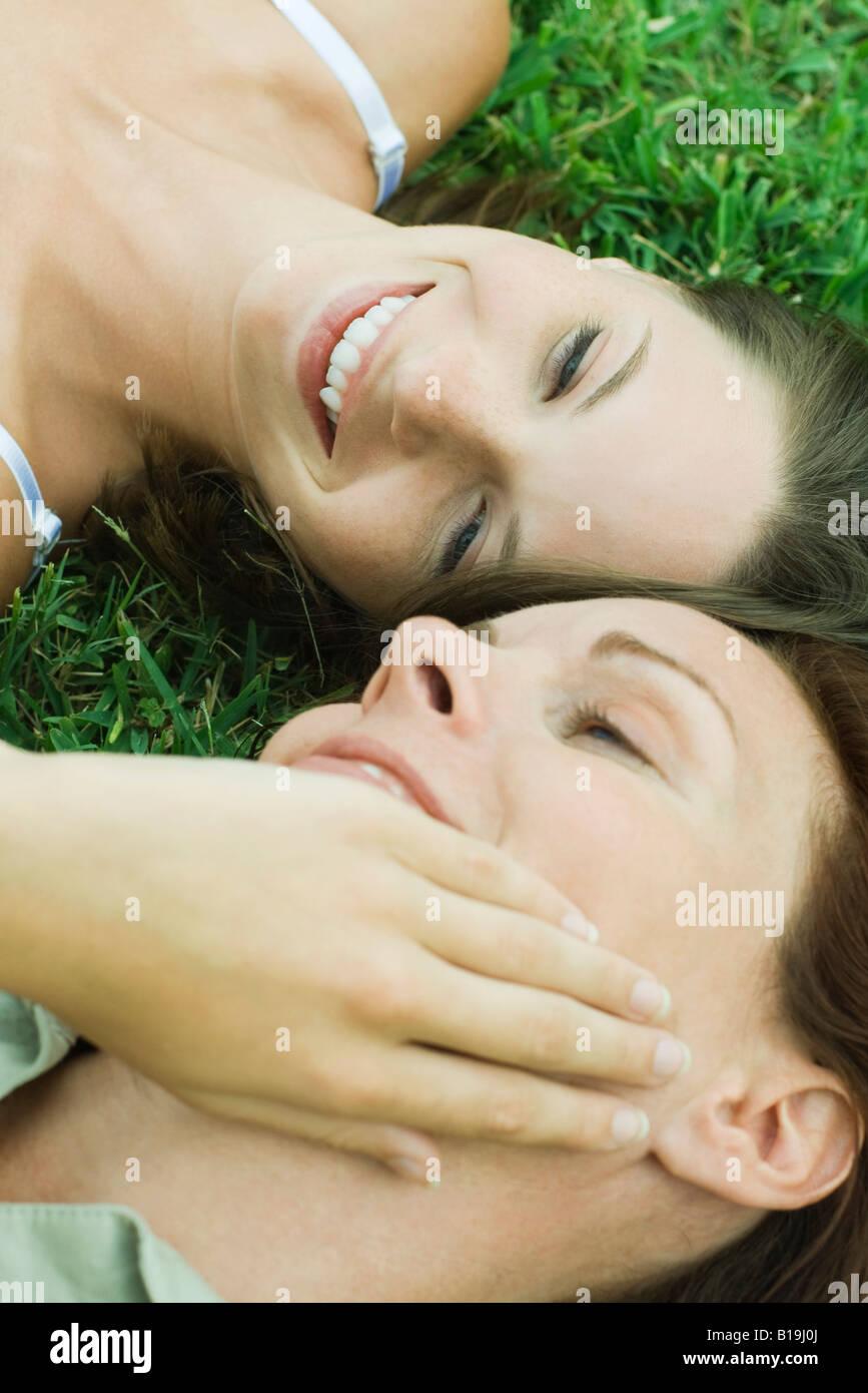 Madre e hija adolescente que yacía en el suelo, niña tocar cara de mujer, vista recortada Imagen De Stock