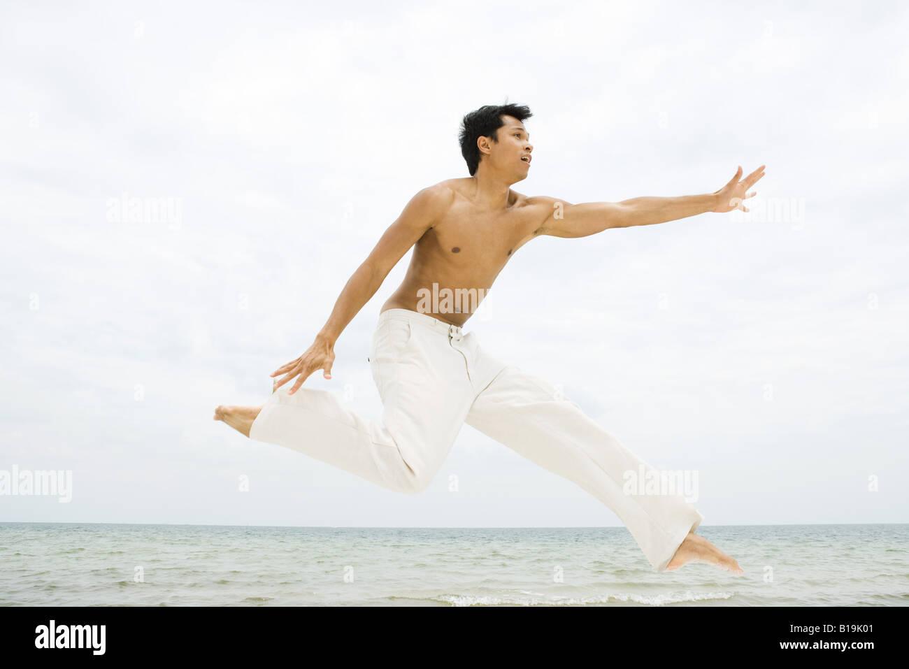 Hombre saltando en el aire, vista lateral, el océano en segundo plano. Imagen De Stock