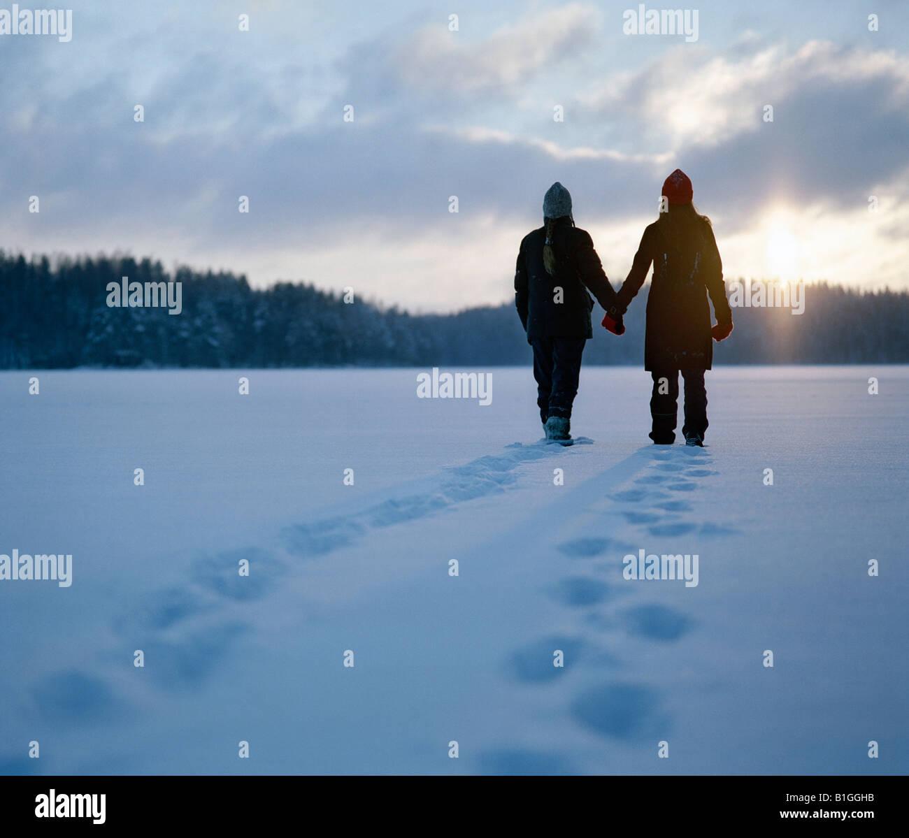 Silueta de dos jóvenes mujeres de pie en la nieve de Finlandia Imagen De Stock