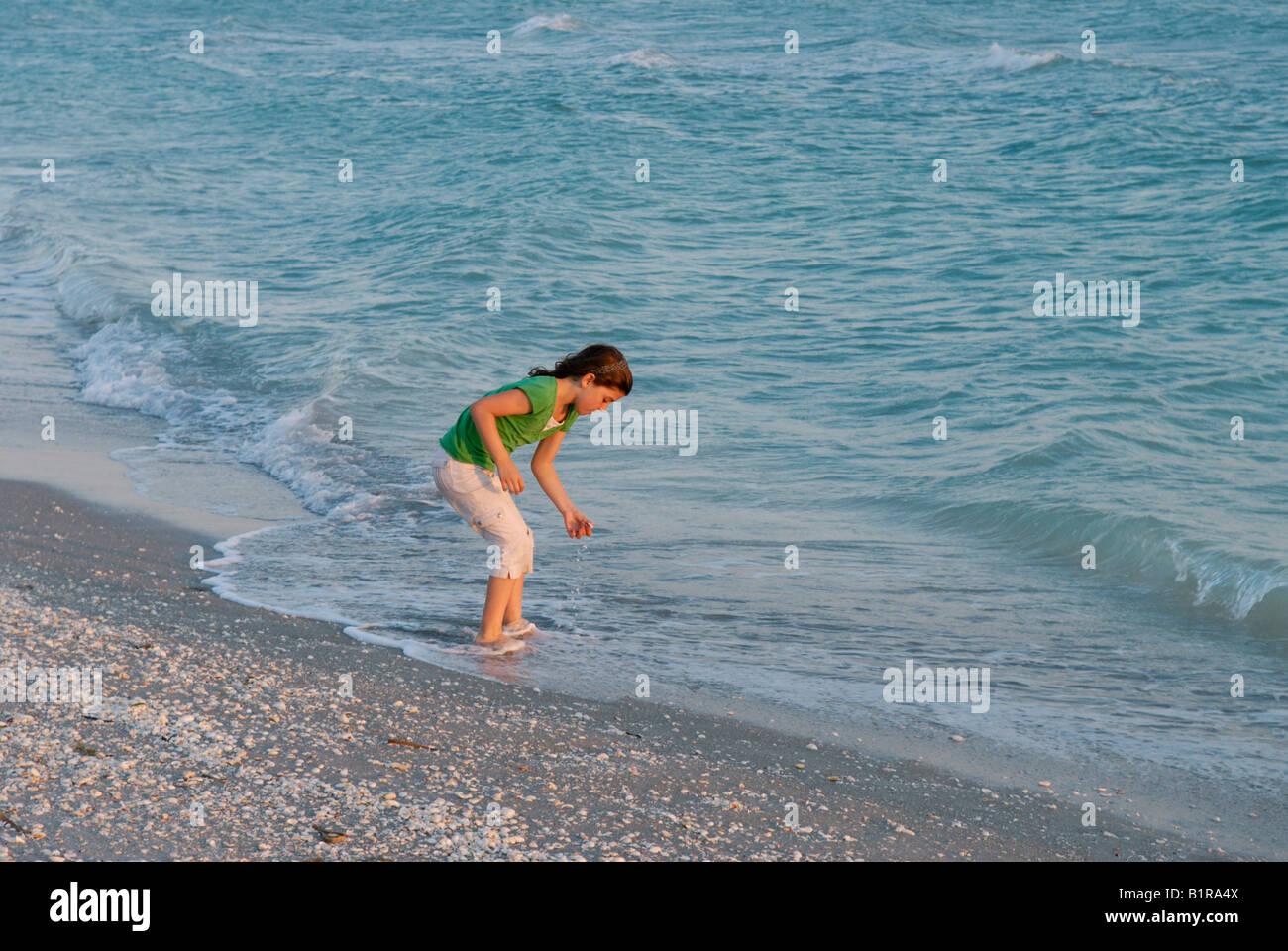 Niña de 9 a 10 años de edad recoger conchas en el borde del agua Bowman's Beach Sanibel Island, Florida Imagen De Stock