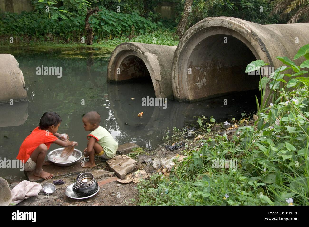Niños lavándose en un tugurio de Calcuta, Calcuta, en Kolkata, Bengala Occidental, India Imagen De Stock