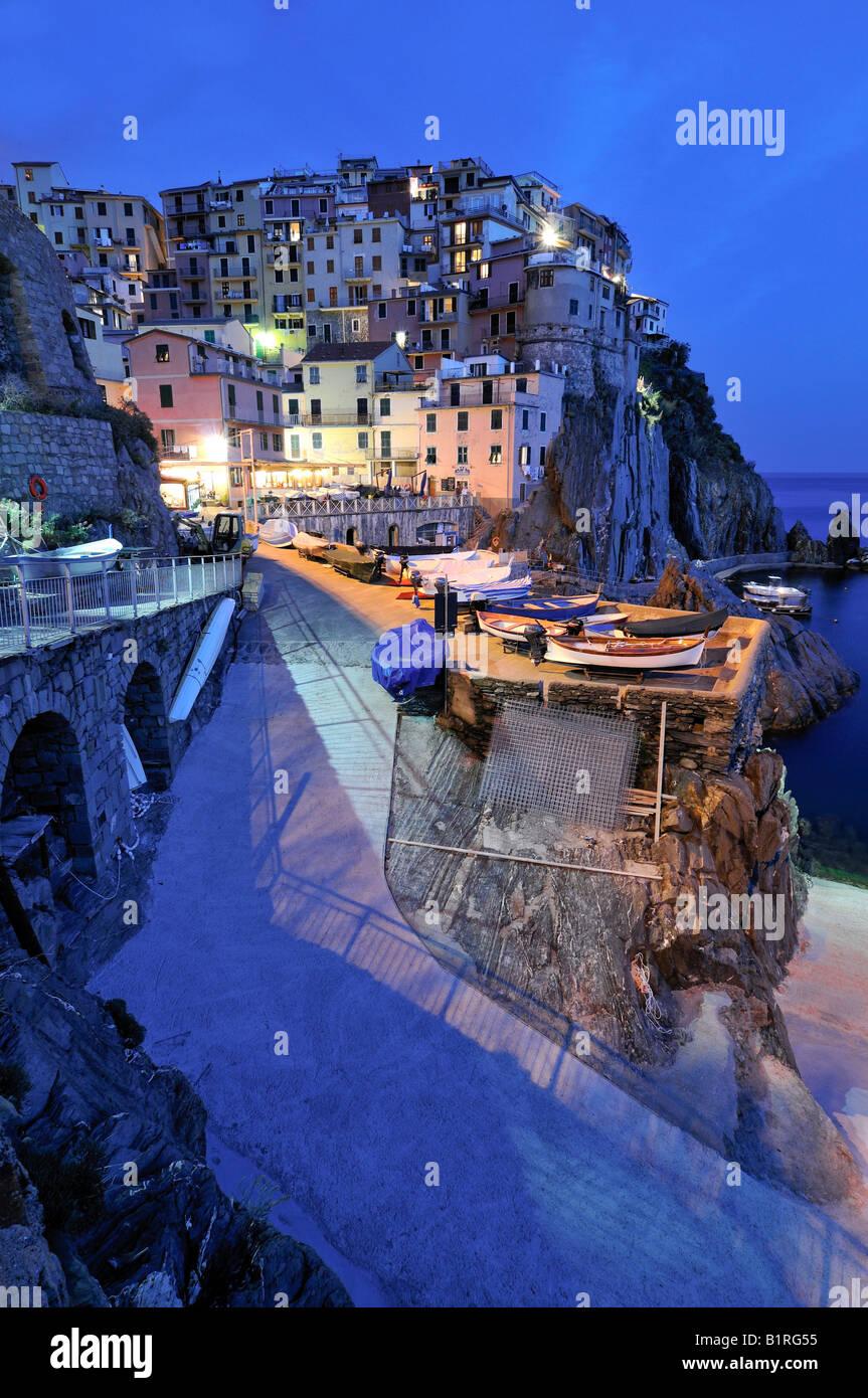 Pueblo de Manarola enclavado en la cima de la costa escarpada al anochecer, Liguria, Cinque Terre, Italia, Europa Imagen De Stock