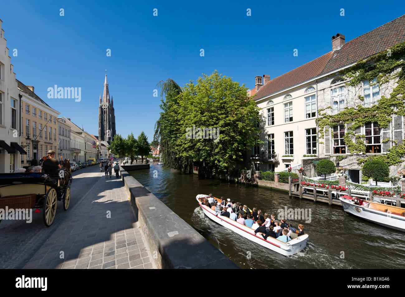 Viaje en barco por el canal, en el viejo centro de ciudad con Onze Lieve Vrouwekerk detrás, Brujas, Bélgica Imagen De Stock