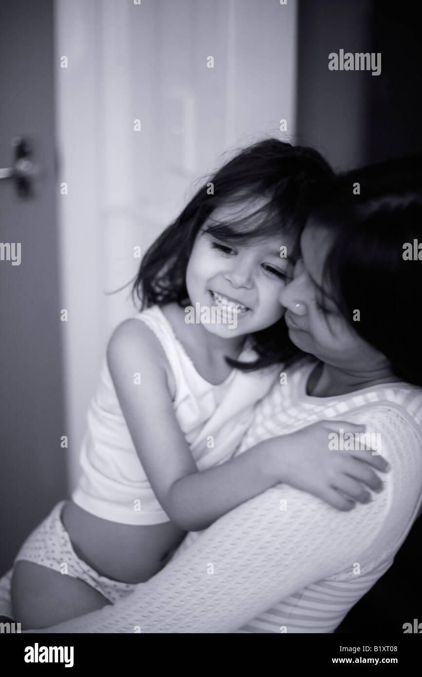 Raza mixta, hija y madre india muchacha envejecida cinco en brazos de su madre Imagen De Stock