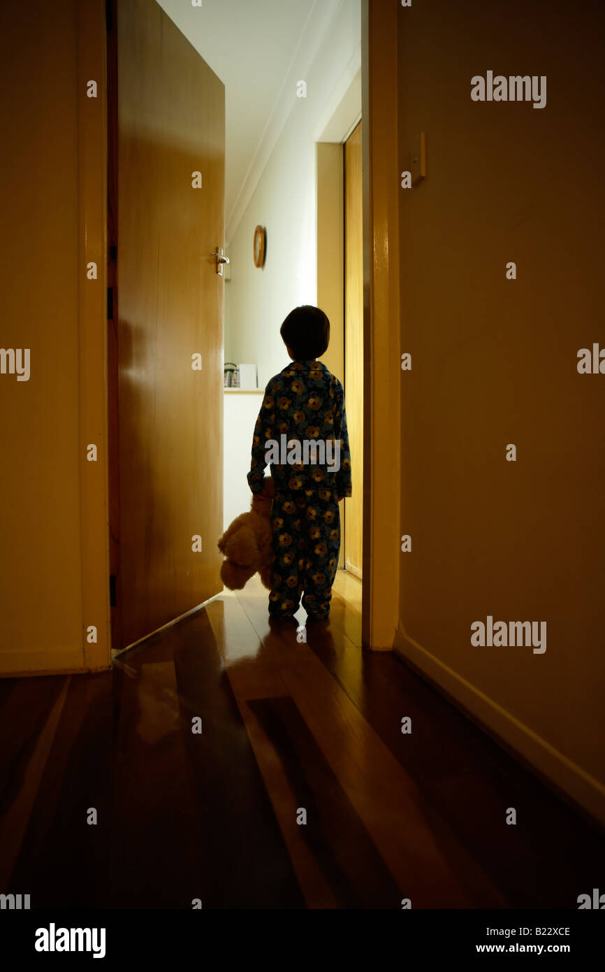 Muchacho de seis años está en el pasillo en pijama con osito de peluche Foto de stock