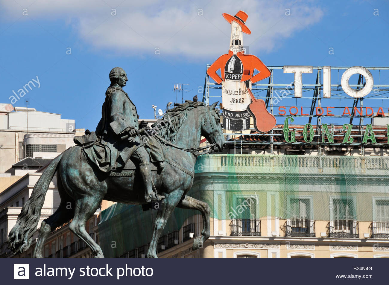 Dos famosos monumentos de Madrid en la Puerta del Sol, el anuncio de Tío Pepe y la estatua ecuestre del rey Imagen De Stock