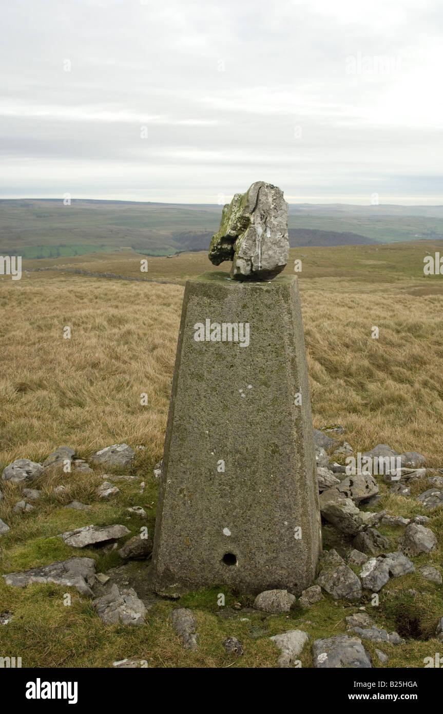 Trig point con una piedra en la cima en Kilnsey Crag en los valles de Yorkshire, Reino Unido Imagen De Stock
