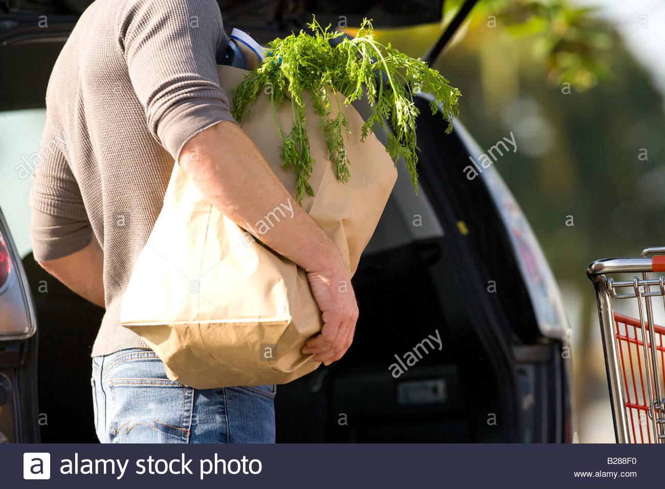 Hombre cargando comestibles en la parte trasera del coche Imagen De Stock
