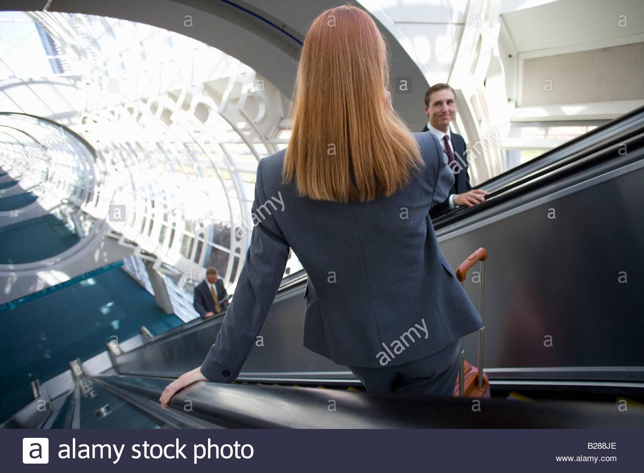 Gente de negocios mediante escaleras mecánicas en el aeropuerto Imagen De Stock