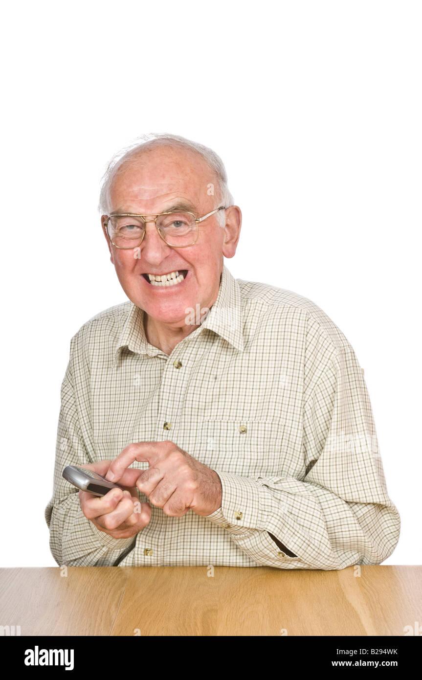 Un anciano frustrándote tratando de texto o utilizar el teléfono móvil con los pequeños botones y números. Foto de stock