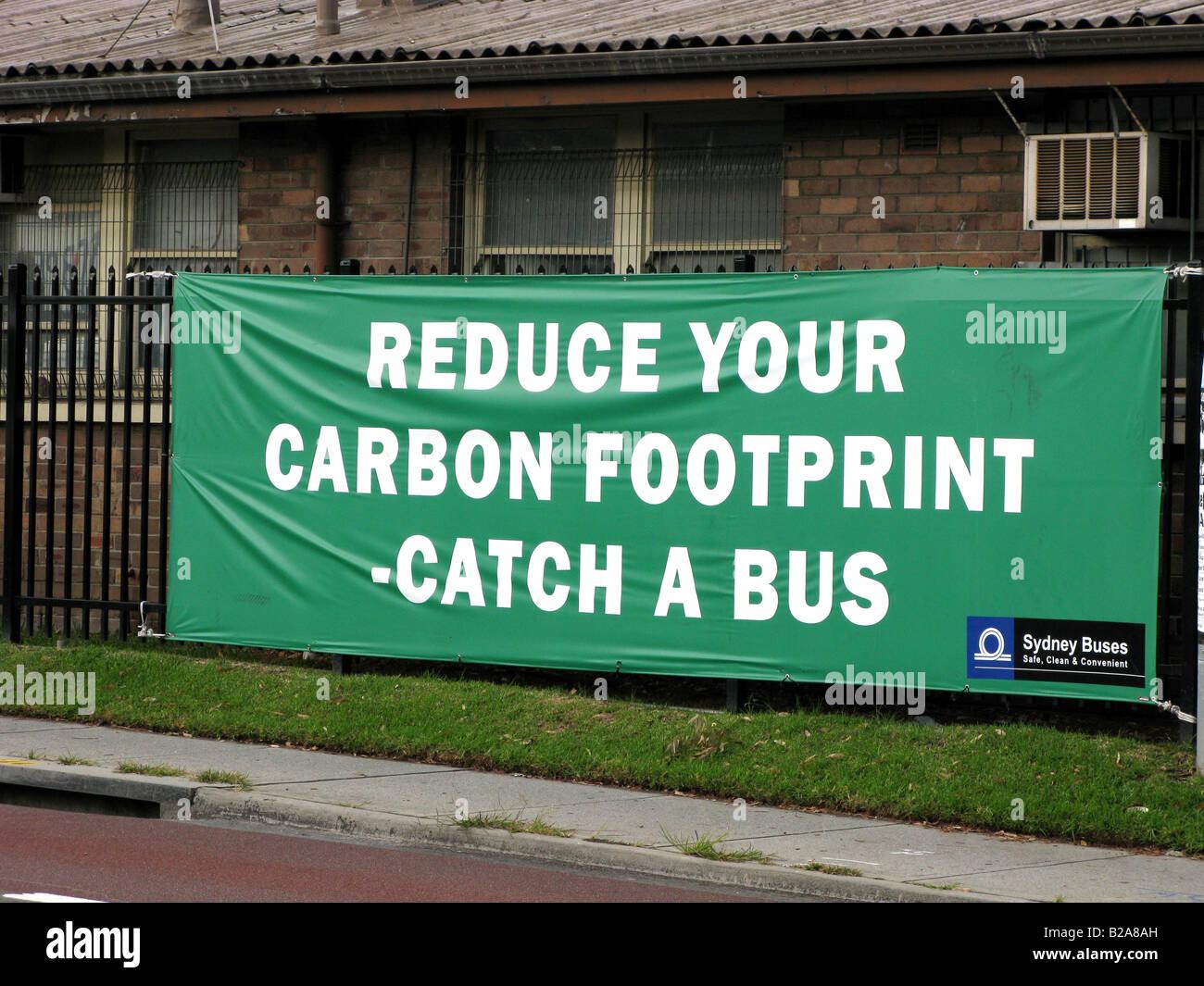 Un signo insta a los viajeros a utilizar los autobuses para el transporte a fin de reducir su huella de carbono Imagen De Stock