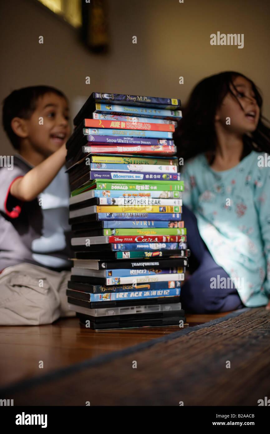 Hermano y hermana mayores de seis a cinco considerar su colección de DVD de raza mixta y caucásicos étnico indio Foto de stock