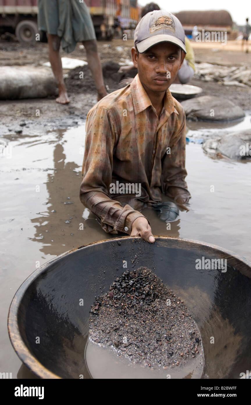 Muchos habitantes de tugurios se ganan la vida reciclando residuos industriales, este trabajador está lavando Imagen De Stock