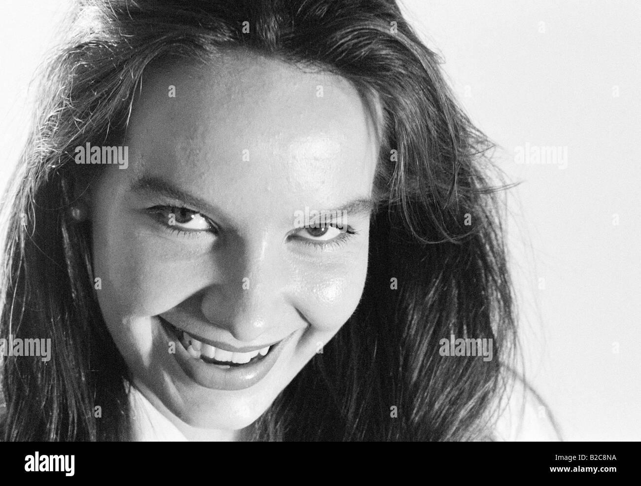 Retrato de mujer joven sonriente, mirando a la cámara. Blanco y negro. Foto de stock