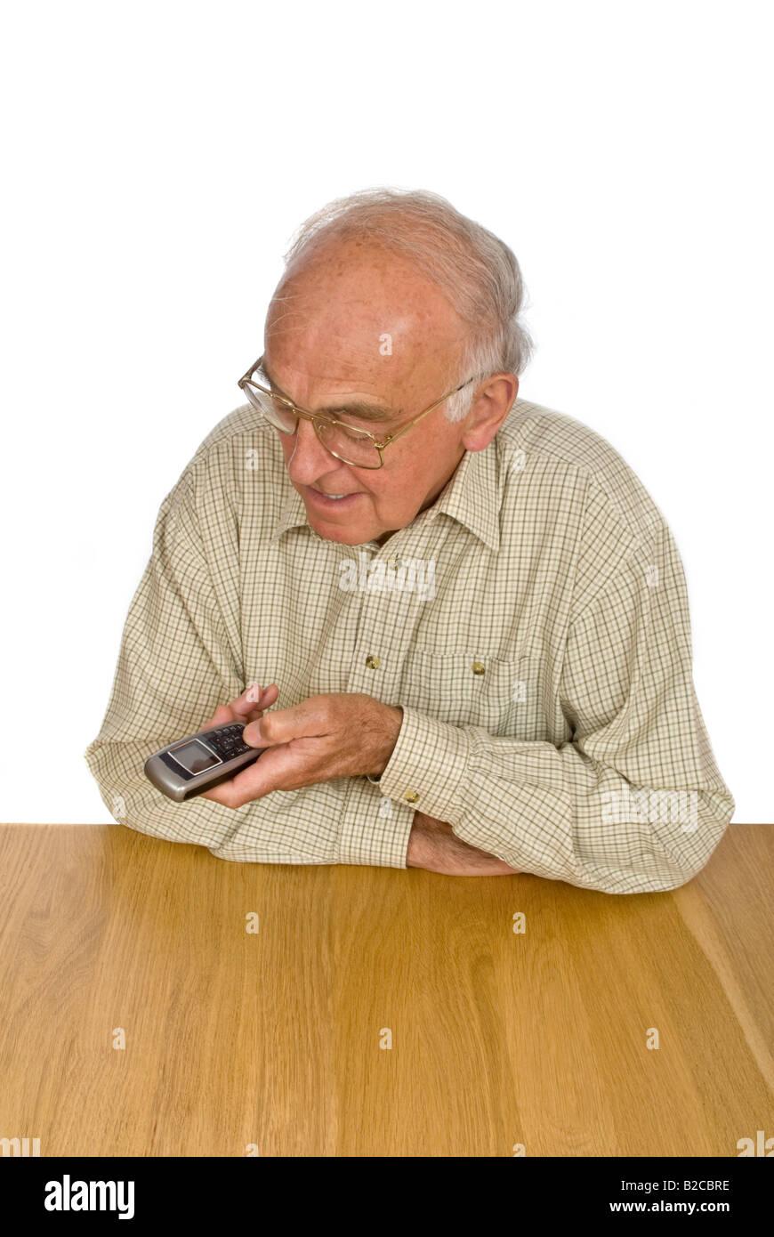 Vertical de un anciano caballero tiene dificultad para ver y utilizar los botones pequeños en un teléfono móvil. Foto de stock